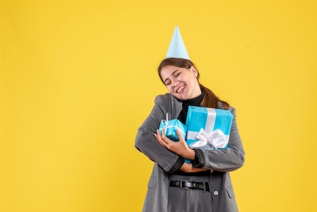 Vorderansicht zufriedenes mädchen mit partykappe, die ihre weihnachtsgeschenke hält