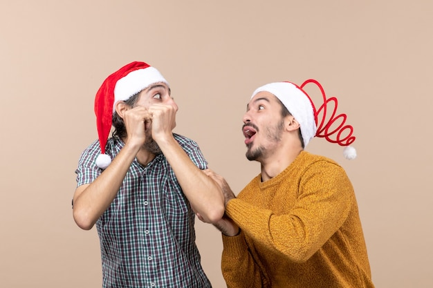 Vorderansicht zwei begeisterte kerle mit weihnachtsmützen, die ihr glück auf beigem isoliertem hintergrund teilen Kostenlose Fotos