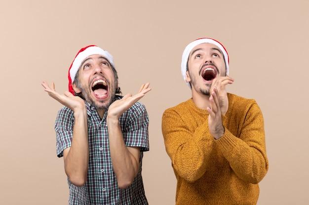 Vorderansicht zwei berauschte kerle mit weihnachtsmützen, die ihre hände klatschen, während sie auf beigem isoliertem hintergrund stehen