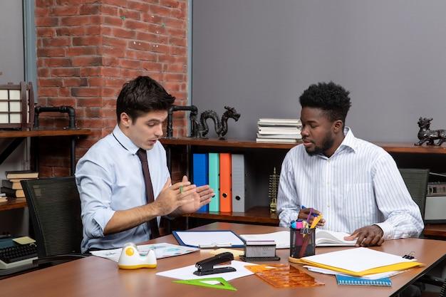 Vorderansicht zwei fleißige geschäftsleute, die am schreibtisch sitzen und das projekt im büro diskutieren
