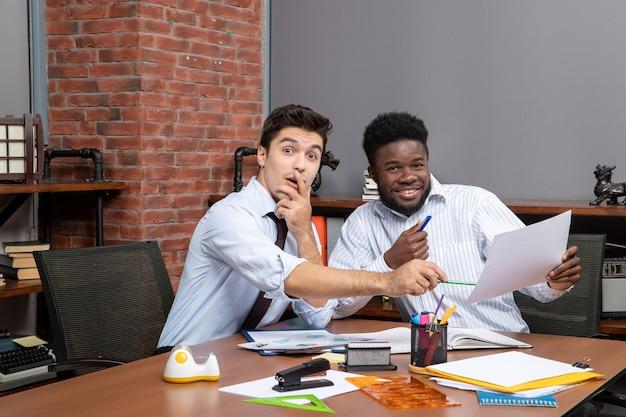 Vorderansicht zwei fröhliche geschäftsleute, die befriedigend zusammenarbeiten, einer von ihnen zeigt auf papier at