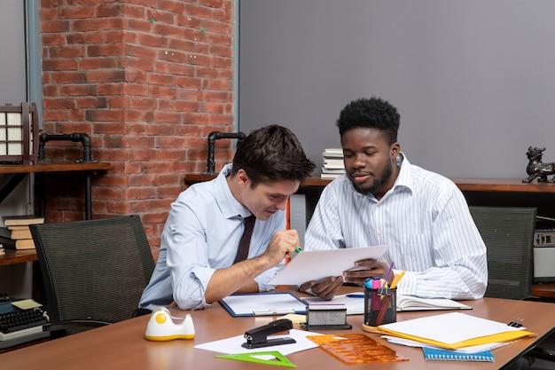 Vorderansicht zwei geschäftsleute diskutieren projektbüromaterialien auf dem tisch
