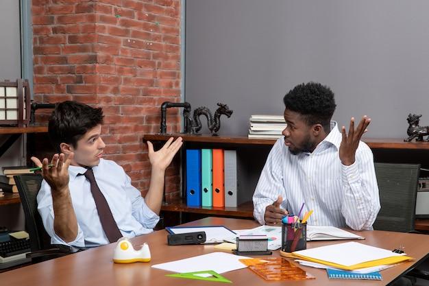 Vorderansicht zwei geschäftsleute in formeller kleidung, die am tisch sitzen und über büromaterialien diskutieren