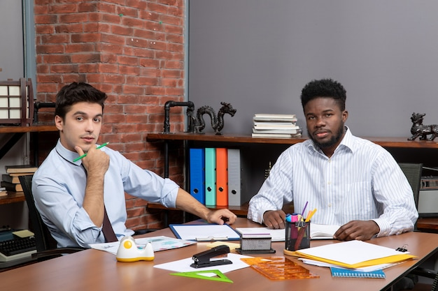 Vorderansicht zwei geschäftsleute sitzen am schreibtisch im büro