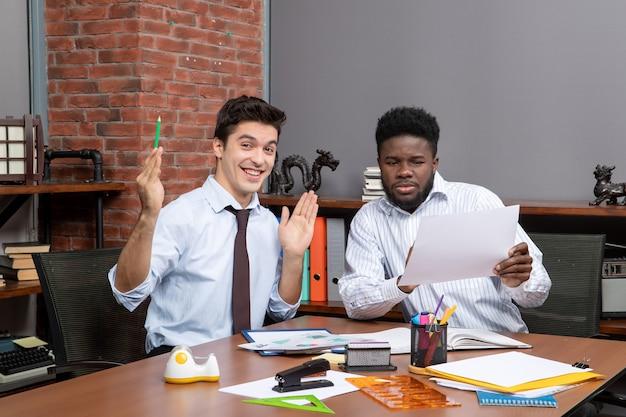 Vorderansicht zwei glückliche geschäftsleute, die die zusammenarbeit zufriedenstellen