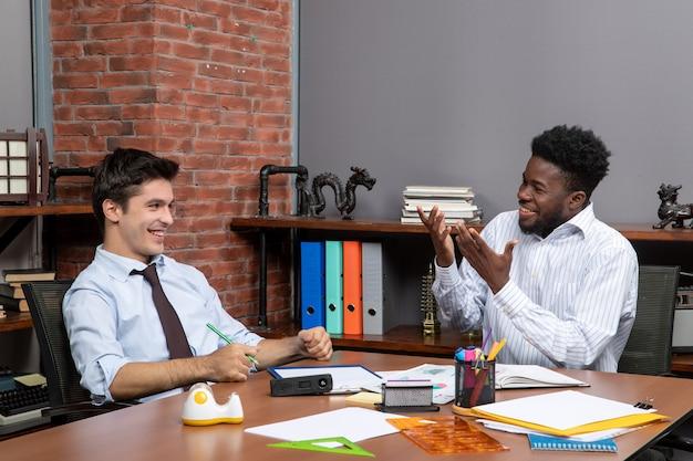 Vorderansicht zwei glückliche geschäftsleute in formeller kleidung, die am schreibtisch sitzen