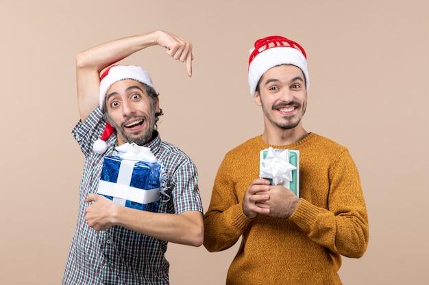 Vorderansicht zwei glückliche kerle, die weihnachtsgeschenke auf beige lokalisiertem hintergrund halten