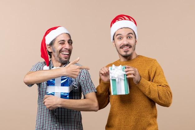 Vorderansicht zwei glückliche kerle, die weihnachtsmützen tragen und geschenke auf lokalisiertem hintergrund halten