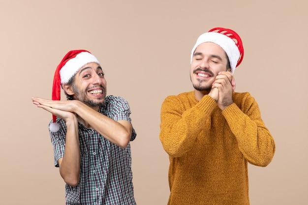 Vorderansicht zwei glückliche kerle mit weihnachtsmützen, einer klatschte in die hände, der andere wünschte mit geschlossenen augen, auf beigem isoliertem hintergrund stehend