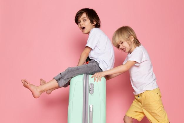 Vorderansicht zwei jungen entzückende niedliche süße spielen in weißen t-shirts auf rosa schreibtisch