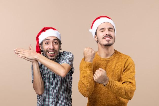 Vorderansicht zwei kerle mit weihnachtsmützen, einer klatschte in die hände, der andere schlug mit geschlossenen augen auf beigem isoliertem hintergrund