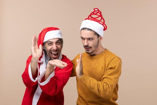 Vorderansicht zwei männer mit weihnachtsmützen, die hände auf beige lokalisiertem hintergrund klatschen