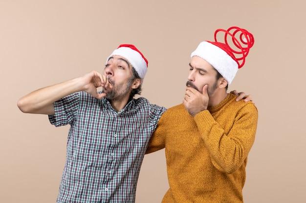 Vorderansicht zwei nachdenkliche kerle mit weihnachtsmützen, die etwas auf beige lokalisiertem hintergrund betrachten