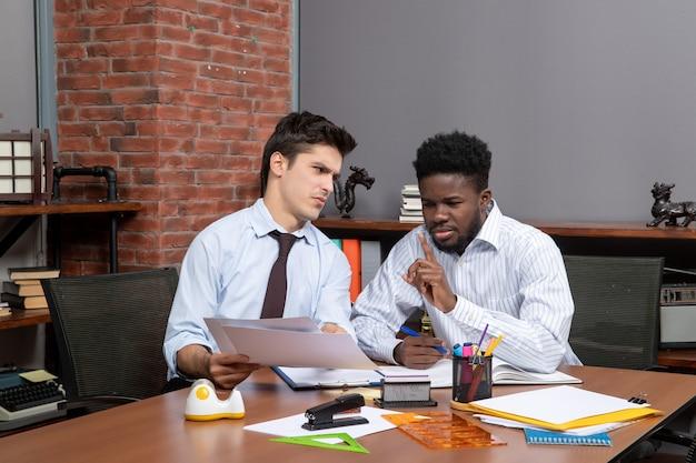 Vorderansicht zwei unermüdliche geschäftsleute diskutieren projekt bei der arbeit