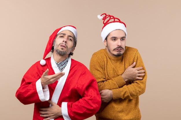 Vorderansicht zwei weihnachtsjungen einer mit santa mantel, aber der andere friert auf beige isoliertem hintergrund ein