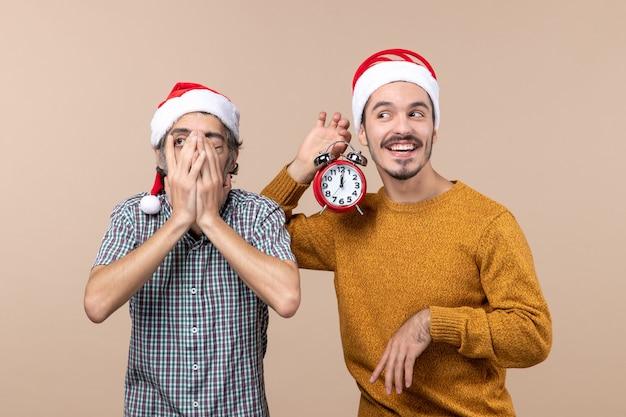 Vorderansicht zwei weihnachtsmänner, die ein auge mit den händen bedecken und das andere einen wecker auf beigem isoliertem hintergrund halten