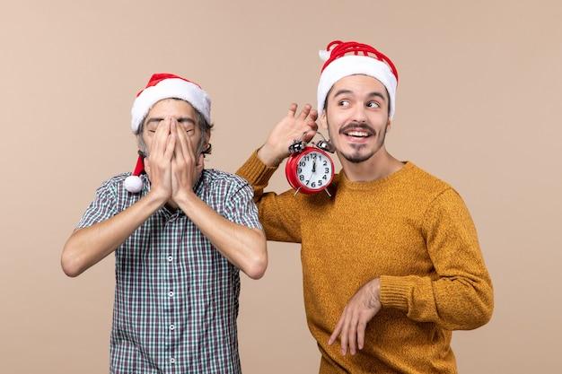 Vorderansicht zwei weihnachtsmänner, die ein gesicht mit seinen händen bedecken und das andere einen wecker auf beigem isoliertem hintergrund halten