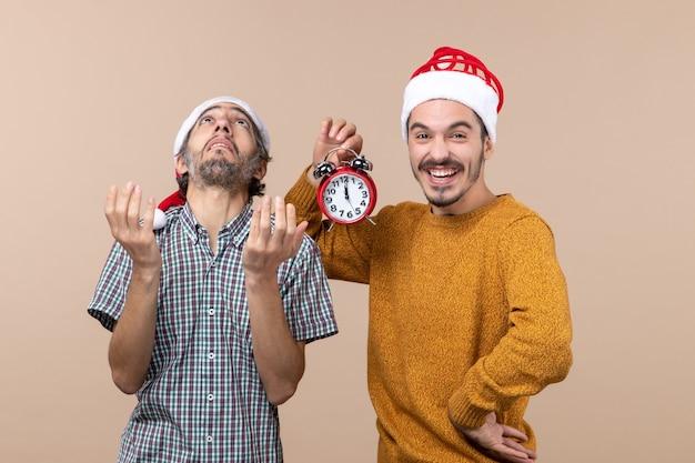 Vorderansicht zwei weihnachtsmänner, die eine decke mit geöffneten händen betrachten und die andere einen wecker auf beigem isoliertem hintergrund halten
