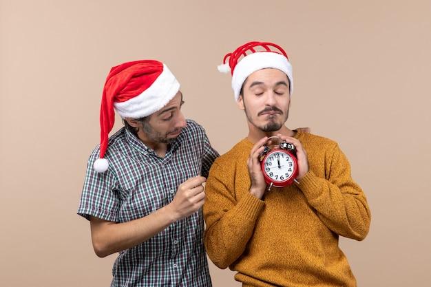 Vorderansicht zwei weihnachtsmänner eins, die einen wecker mit beiden händen auf beige lokalisiertem hintergrund halten