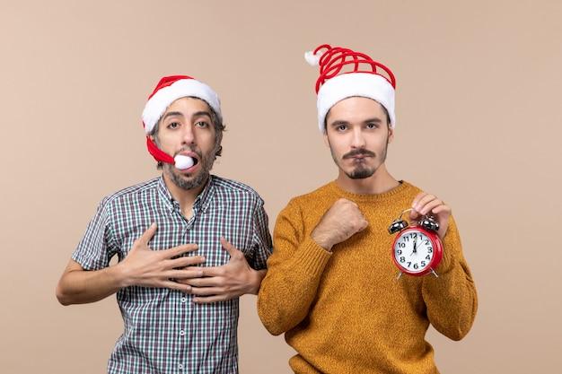 Vorderansicht zwei weihnachtsmänner, von denen einer hände an seine brust legt und der andere einen wecker auf beigem isoliertem hintergrund hält