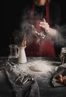 Vorderansichtbäcker, der hände vom mehl entfernt