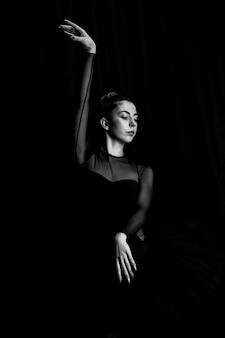 Vorderansichtballerina, die in der dunkelheit aufwirft