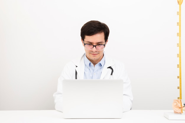 Vorderansichtdoktor, der an einem laptop arbeitet
