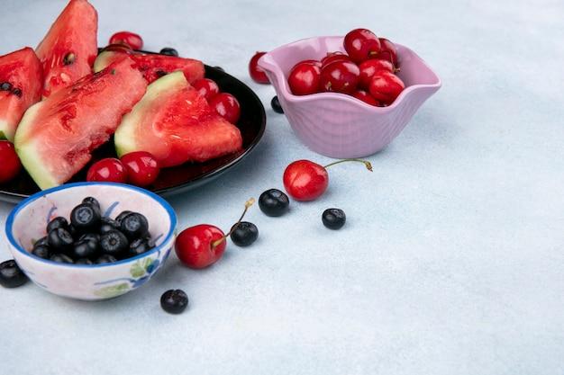 Vorderansichten scheiben der wassermelone auf einem teller mit blaubeeren und kirschen