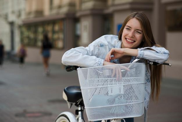 Vorderansichtfrau, die am fahrradlenker sich lehnt