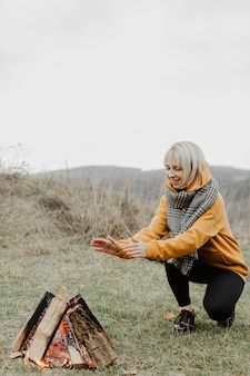 Vorderansichtfrau, die am lagerfeuer sich wärmt