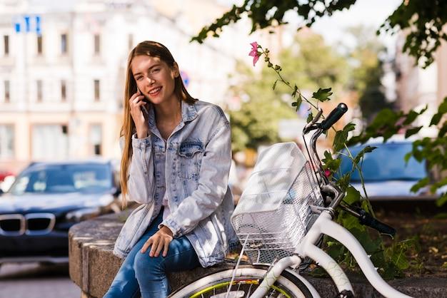 Vorderansichtfrau, die am telefon nahe bei fahrrad spricht