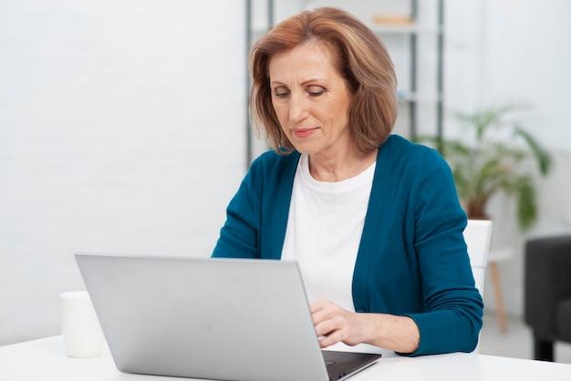 Vorderansichtfrau, die an einem laptop arbeitet