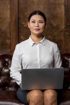 Vorderansichtfrau, die an laptop arbeitet
