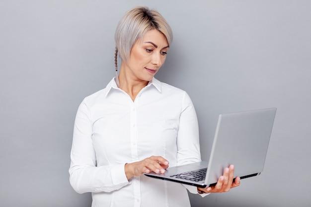 Vorderansichtfrau, die auf laptop schaut