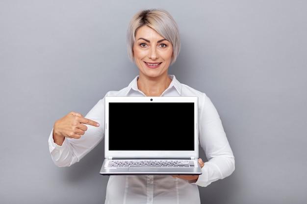Vorderansichtfrau, die auf laptop zeigt