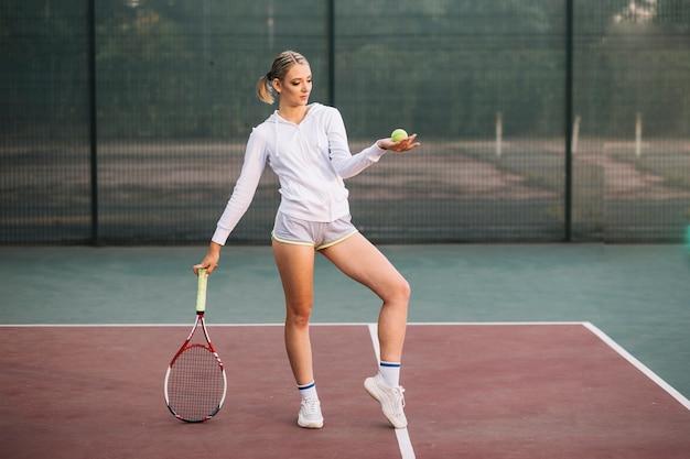 Vorderansichtfrau, die auf tennisfeld aufwirft