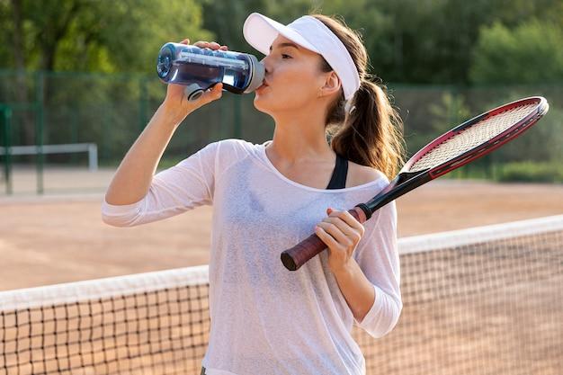 Vorderansichtfrau, die auf tennisplatz hydratisiert