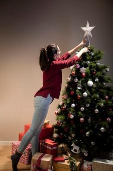 Vorderansichtfrau, die auf weihnachtsbaum den stern setzt