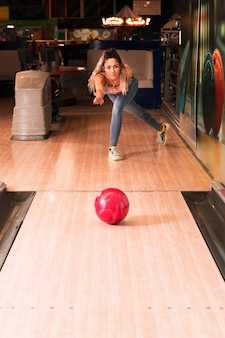 Vorderansichtfrau, die bowlingspiel spielt
