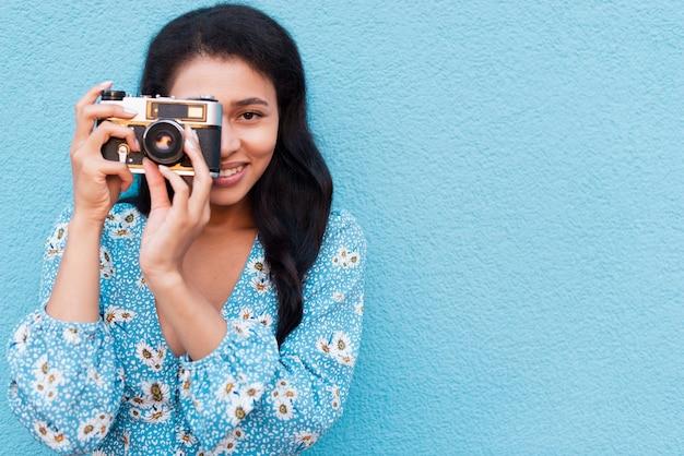 Vorderansichtfrau, die ein foto macht und kamera betrachtet