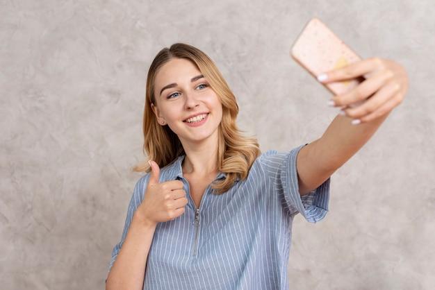 Vorderansichtfrau, die ein selfie mit ihrem telefon nimmt