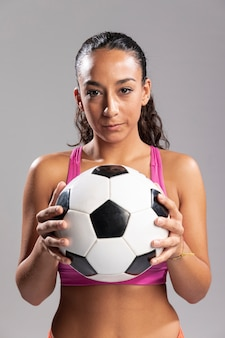Vorderansichtfrau, die fußball hält