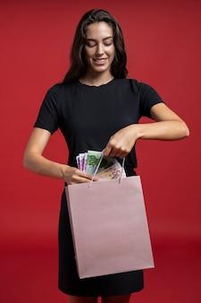 Vorderansichtfrau, die geld in ihre einkaufstasche einsetzt