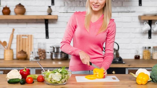 Vorderansichtfrau, die gemüsepaprika in der küche schneidet