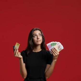 Vorderansichtfrau, die ihr einkaufsgeld mit kopienraum zeigt