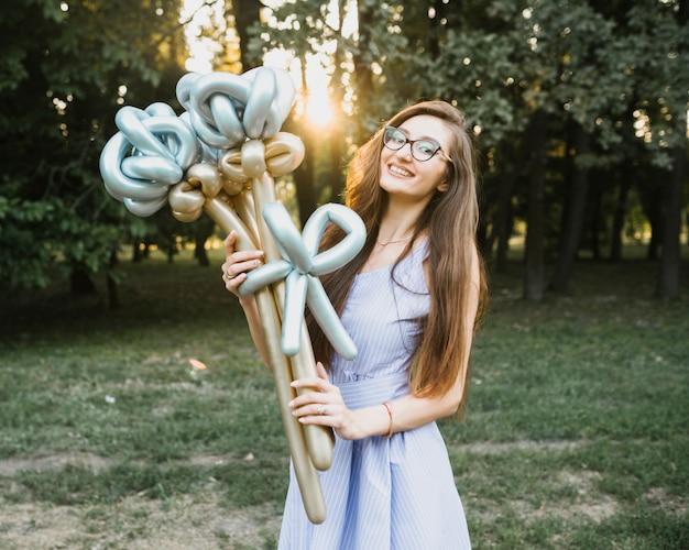 Vorderansichtfrau, die im sonnenlicht ballone hält