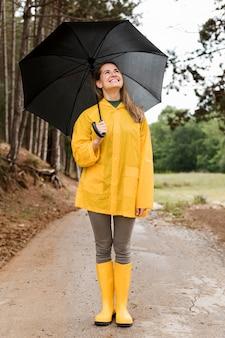 Vorderansichtfrau, die im wald steht, während sie einen regenschirm hält