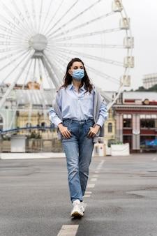 Vorderansichtfrau, die in einem vergnügungspark beim tragen einer medizinischen maske aufwirft