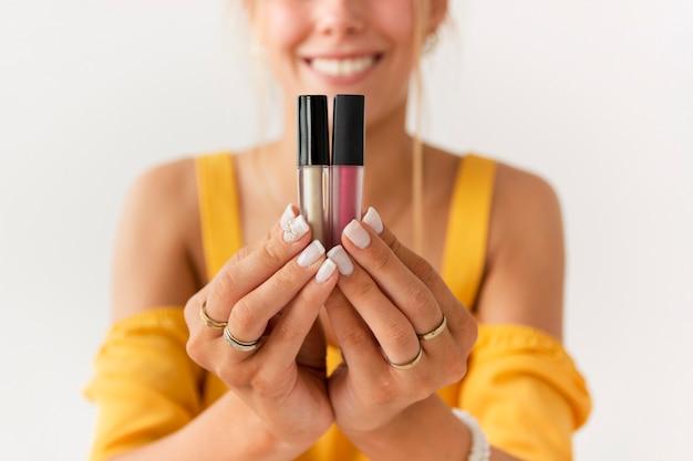 Vorderansichtfrau, die lipgloss darstellt