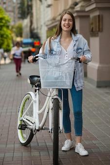Vorderansichtfrau, die mit fahrrad aufwirft